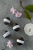 Blown eggs painted black and decorated with lace ribbon