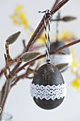 Blown egg painted black and decorated with lace ribbon