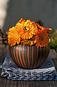 Posy of pot marigolds in rounded vase