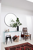 Vase of leafy branches on glass console table, stool, basket and chair in foyer