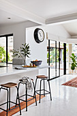 Marble breakfast bar with bar stools in white, open-plan interior