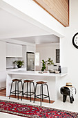 Marble breakfast bar and bar stools in open-plan kitchen