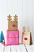 Gift boxes and bags decorated with pompoms and antlers