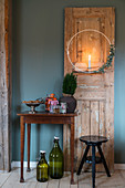 Wreath with candle on old wooden door next to table and stool