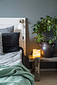 Bed with DIY headboard and houseplant on bench used as bedside table