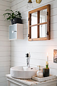 Washstand with round countertop sink in bathroom with white wooden wall