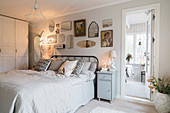 Collection of mirrors above bed in vintage-style, white bedroom