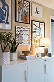 Gallery of graphic artworks above sideboard