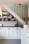 Sideboard and shelving modules on wall below staircase in white interior