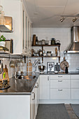 Country-house kitchen with stainless steel worksurfaces and white cabinets