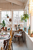 Rustic vintage-style decorations and plants around dining table in conservatory