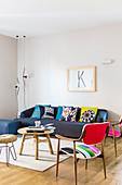 Dunkelblaues Sofa mit bunten Zierkissen davor Holztisch, Hocker und Fifties-Stühle