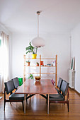 Dining table and black leather chairs in front of shelves