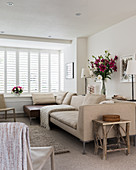 Beige sofa and louvre windows in living room in natural shades