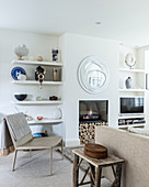 Shelves flanking built-in fireplace in white and beige living room