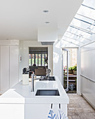 Island counter and skylights in white, modern kitchen