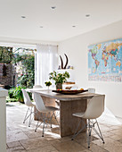 Shell chairs at table in modern dining room with access to garden