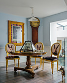 Yellow Baroque chairs with animal motifs on backrests around antique pedestal table