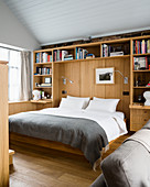 Bed in niche surrounded by fitted wooden shelves