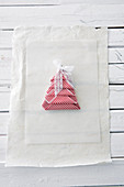 Linen napkin folded into Christmas-tree shape and decorated with lace ribbon