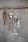 Rustic dreamcatchers hung from branch on grey wall