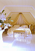 Opulent bed with canopy and ruffles in attic room