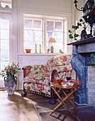 Floral armchair between open fireplace and lattice window