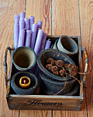 Purple candles and rustic plant pots in old wooden crate