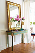 Gilt-framed mirror, vase of peonies and table lamps on antique console table