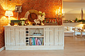 Festively decorated, rustic, white sideboard against brick wall in cosy interior