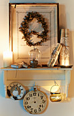 Vintage-style, candle-lit, still-life arrangement on wall-mounted shelf