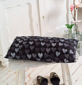 Black cushion with white polka-dots and stamped pattern of hearts