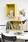 Shelf modules made from wooden crates painted yellow above desk