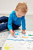 Kleiner Junge beim Bemalen der Rückseite eines Kinderpuzzles