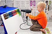 Little boy melting wax crayons on canvas using hairdryer