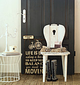 Old, shabby-chic farmhouse chair against black panelled door