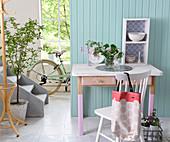 Alter Schreibtisch mit rosa bemalten Beinen vor hellblauer Bretterwand