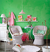 White-painted wicker easy chairs against green wall with pretty accessories