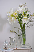 Arrangement of white amaryllis and waxflwoers
