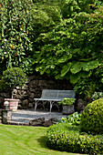 Bench against rustic stonewall in lush, green, well-tended garden