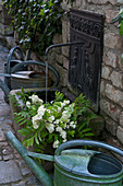 Metal watering cans next to waterspout with stone trough and flowing water