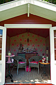 Floral wallpaper, side tables and wicker chairs in summerhouse