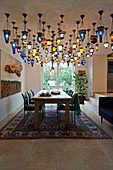 Multiple Oriental ceiling lamps above dining table in open-plan interior
