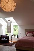 Armchair below skylights in bedroom with sloping ceiling