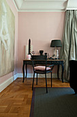 Black chair at Baroque console table against pink wall
