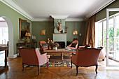 Baroque armchairs in classic living room with pale green walls