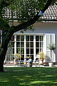 Seating area in summery garden outside house with lattice windows