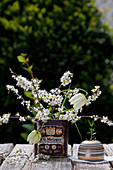 Snake's head fritillaries and branches of blackthorn blossom in old tin