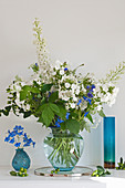 Lavish blue-and-white flower arrangement of phlox, delphiniums and raspberry stems