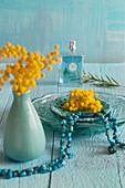 Glasteller, Keramik, türkisfarbene Kette und Mimosen
